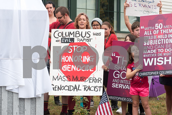 A ceremony was held on Monday morning at the Southington Municipal Center for the dedication and unveiling of the Christopher Columbus Monument honoring the 525th anniversary of the discovery of America. Protestors hold signs behind the statue of Columbus about to be unveiled.