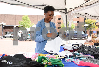 10/11/17  Wesley Bunnell | Staff  The owner of DribbleBabies Children's Clothing Store, Davina Ismail, sets up her stand at the New Britain Farmers' Market in Central Park on Wednesday at noon.