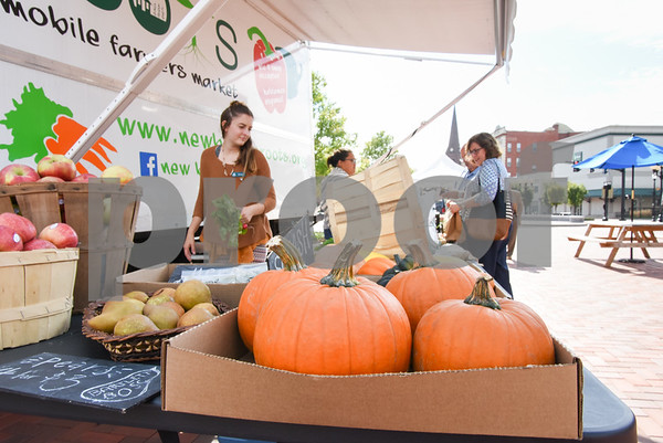 10/11/17 Wesley Bunnell   Staff Monica Houghton helps stock fresh produce at the New Britain ROOTS mobile farm stand at the New Britain Farmers' Market in Central Park on Wednesday afternoon. Monica is a Food Corp Service member who is working with ROOTS for one year.