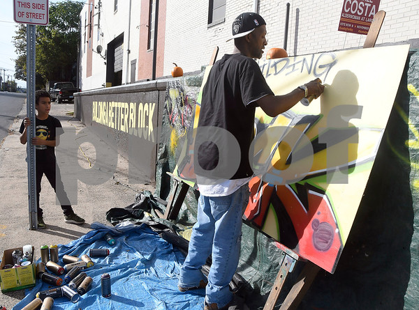 10/21/2017 Mike Orazzi | Staff Jaqwon Dowd watches as Carthel Hueston works on a mural during a block party in the area of Church and East Streets Saturday afternoon in New Britain.