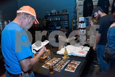 10/25/17  Wesley Bunnell | Staff  The New Britain Industrial Museum held a bier fest fundraiser at Alvarium Beer Company on Wednesday evening. Brien Balavender, President of B&J Construction looks over the New Britain themed books for sale.