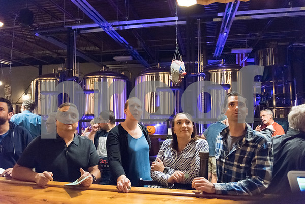 10/25/17 Wesley Bunnell | Staff The New Britain Industrial Museum held a bier fest fundraiser at Alvarium Beer Company on Wednesday evening. Looking over the beer selection with a halloween decoration hanging above them are Greg Goodstein, Sara Lavery, Olivia Fiducia and Mike Farrell.