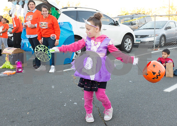 10/27/17 Wesley Bunnell | Staff The Foster Care Unit & Fatherhood Leadership Team of the State of CT Department of Children and Families held a trunk-or-treat for children on Friday evening with volunteers in costume and passing out candy from decorated cars. A trunk-or-treater twirls around with her candy bucket and bubble maker.