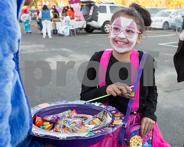 10/27/17  Wesley Bunnell | Staff  The Foster Care Unit & Fatherhood Leadership Team of the State of CT Department of Children and Families held a trunk-or-treat for children on Friday evening with volunteers in costume and passing out candy from decorated cars. Yeliskeeth Calderon, age 8, smiles as she looks up at Ann Baldwin from Baldwin Media passing out candy.