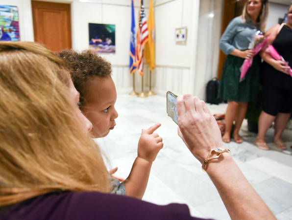 10/10/18 Wesley Bunnell | Staff Coordinator of Fine Arts for CSDNB Leona Clerkin shows 2 year old Corbin Tsantiris how to use the phone to take a photo of his mother, CSDNB Art Teacher Kristina Tsantiris, on Wednesday afternoon. Artwork from CSDNB art teachers is in display at City Hall through November 20th on the second floor as part of Leading by Example III. The exhibit is sponsored by Mayor Erin Stewart's Art in the Heart of the City series and the New Britain Britain Commission on the Arts.
