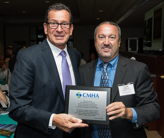 10/18/18 Wesley Bunnell | Staff CMHA held their 2018 Annual Meeting at their new location at on Main St in New Britain on Thursday evening featuring a special award to Governor Dannel Malloy for his help in procuring their new building. Governor Malloy receives his award from Chairmon of the Board of Directors Todd DeGroff.