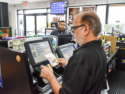 10/22/18  Wesley Bunnell | Staff  Manager Iqbal Khan of the Sunoco Gas Station at 737 West Main St helps customer Jonathan Colon with his lottery purchases on Monday afternoon.