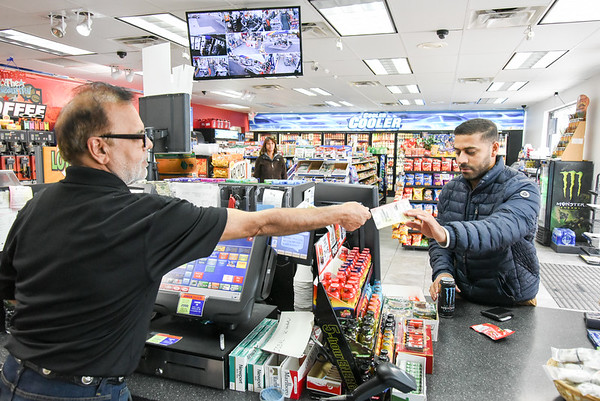 10/22/18 Wesley Bunnell | Staff Manager Iqbal Khan of the Sunoco Gas Station at 737 West Main St hands customer Jonathan Colon his lottery purchases on Monday afternoon.