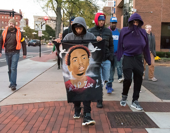 10/24/18 Wesley Bunnell | Staff A rally was held at Central Park on Wednesday evening calling for the release of police video from the December 14 2017 New Britain Police shooting which resulted in the death of Zoe Dowdell of Bloomfield. Step brother Hakeem Robinson holds a banner with Zoe's likeness as he leads the march from Central Park to police headquarters.
