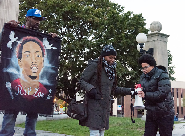10/24/18 Wesley Bunnell | Staff A rally was held at Central Park on Wednesday evening calling for the release of police video from the December 14 2017 New Britain Police shooting which resulted in the death of Zoe Dowdell of Bloomfield. Zoe's father Shawn Dowdell holds a banner with the Zoe's likeness as step mother Deanna Dowdell hands the megaphone back to activist Kerry Ellington.