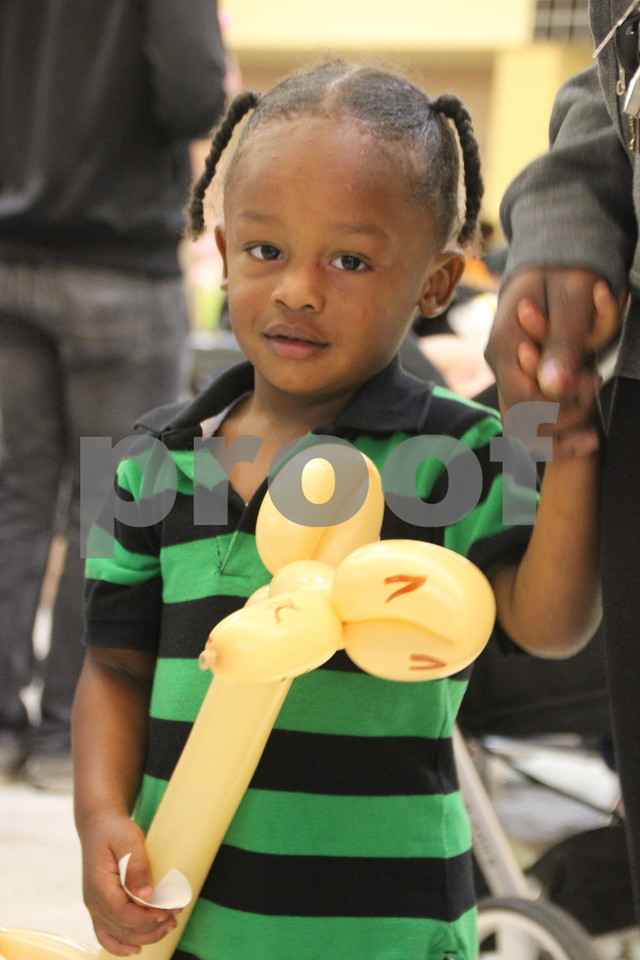 """Crossroads Mall was filled with vendors of every kind offering opportunities to learn lots of things, have some candy, and play games. On Saturday, October 24, 2015, Crossroads Mall in Fort Dodge held the Kidzmania event. Here's Kaveon Claytor (in the green striped shirt)  holding a balloon creation made by """"Maude"""", the clown, one of several balloon artists on hand to entertain those attending the event."""