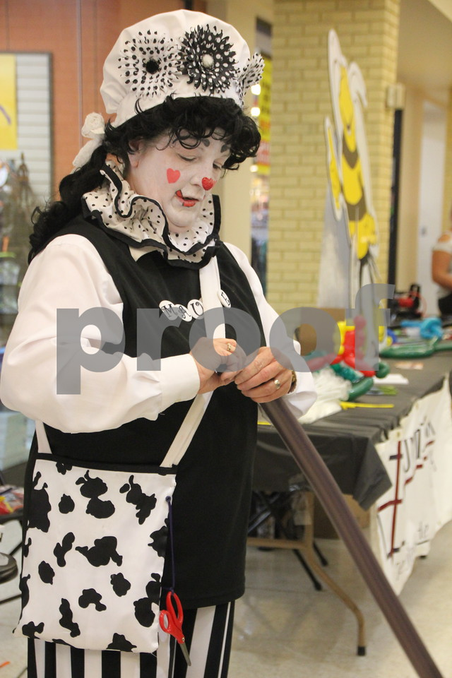"""On Saturday, October 24, 2015, Crossroads Mall in Fort Dodge held the Kidzmania event. The Mall was filled with vendors of every kind offering opportunities to learn lots of things, have some candy, and play games. Seen here making a balloon creation is """"Maude"""", the clown, one of several  balloon artists on hand to  entertain those attending the event."""