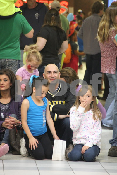 Crossroads Mall was filled with vendors of every kind offering opportunities to learn lots of things, have some candy, and play games. On Saturday, October 24, 2015, Crossroads Mall in Fort Dodge held the Kidzmania event. Pictured here in the crowd is John Daniels  kneeling and near the front row(in the Iowa Hawkeyes jacket between the girl in the blue shirt on the left and the girl in the yellow shirt on the right) watching  one of many acts appearing at center stage in the Crossroads Mall.