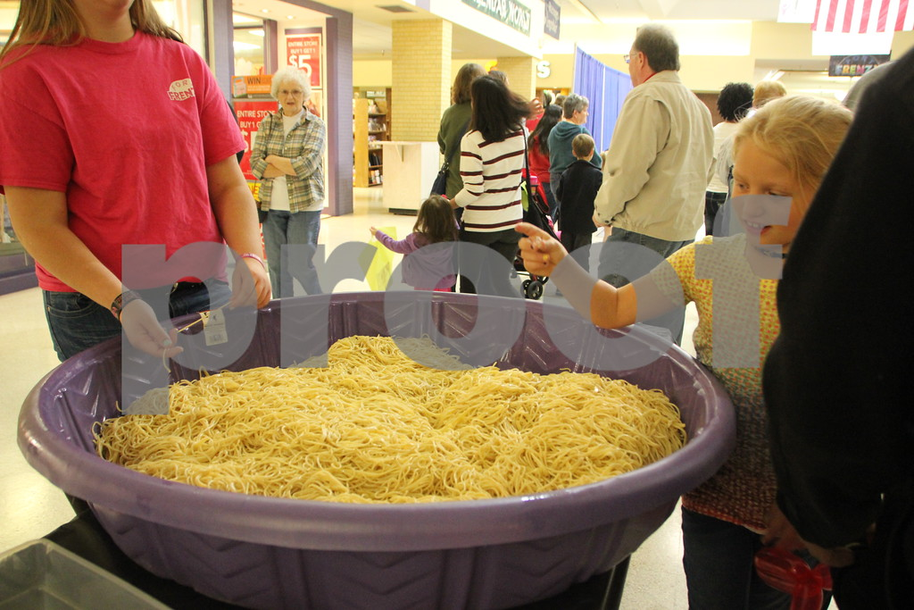 On Saturday, October 24, 2015, Crossroads Mall in Fort Dodge held the Kidzmania event.  Seen here(on the right in the yellow shirt)  having fun is : Kaylynn Hoover. The objective here was to locate  some glass -like  pebbles in the spaghetti and give it to the attendant who then gives them a prize for finding it.
