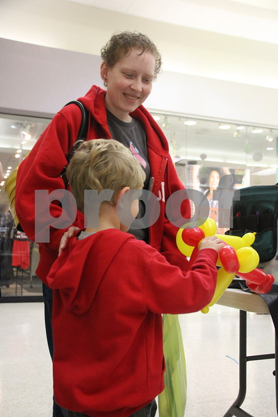 On Saturday, October 24, 2015, Crossroads Mall in Fort Dodge held the Kidzmania event. The Mall was filled with vendors of every kind offering opportunities to learn lots of things, have some candy, and play games. Pictured here taking their turn for a balloon creation is Gus Powvens ( in the red jacket and holding the balloon).