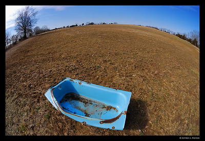No Privacy February 24, 2007  Nikon D80 w/10.5mm Nikkor (f11, 1/160 sec, ISO 100)  I have no clue why this cast-iron blue bathtub was sitting out in the middle of this field.  This image makes it look like someone is ready to set sail in this tub.