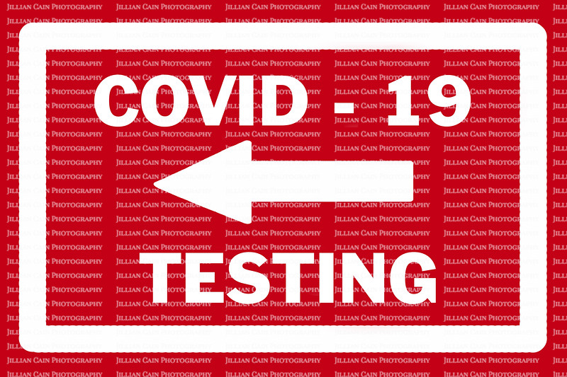 COVID - 19 TESTING sign with white arrow pointing to the left against a red background.