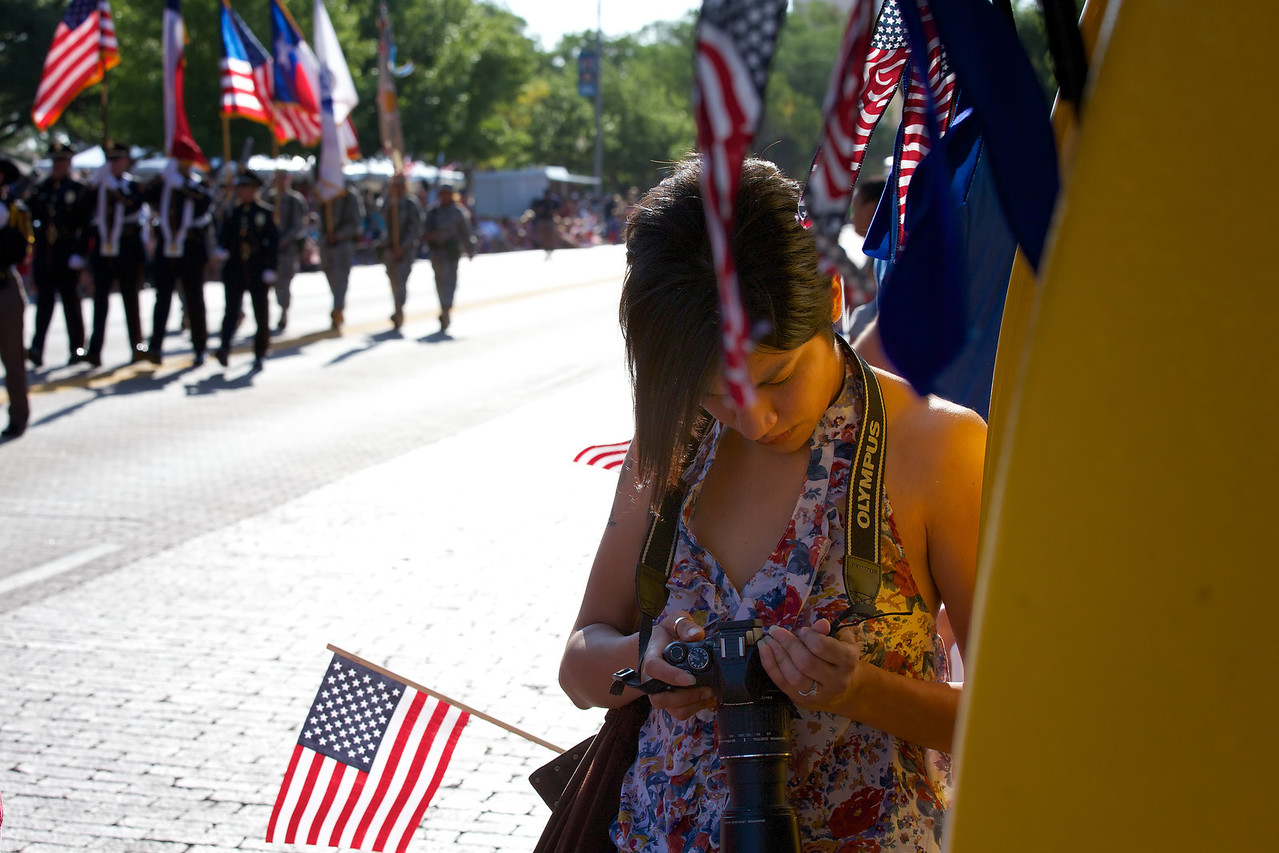 Photography student checking her camera as the 4th of July parade begins in Lubbock, Texas 2012.