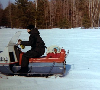Joanna taking her dachshund for a snowmobile ride, 1972