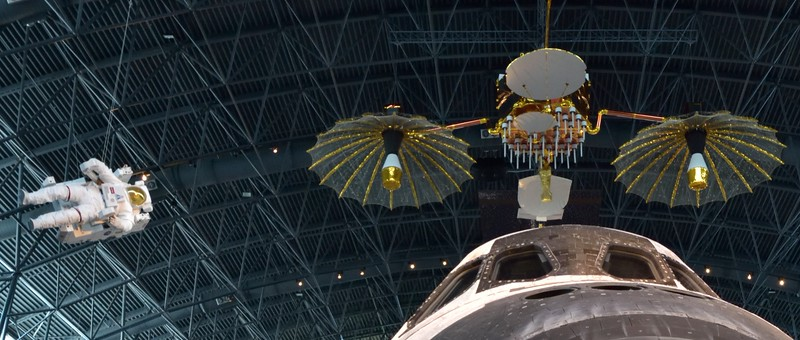 A Manned Maneuvering Unit hangs above Discovery alongside a<br /> Replica Communications Satellite.<br /> Three Tracking and Data Relay Satellites (TDRS) were placed into geosynchronous orbit to provide contact with spacecraft in low Earth orbit<br /> <br /> Smithsonian Udvar- Hazy Center, Washington