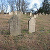 In the center of this photo: the gravestone of Ebenezer Bass on the right, and that of his wife on the left. To locate the graves, enter the cemetery by the gate and walk straight in, uphill, to the eighth row. The Bass graves will be about 4 stones to your right.