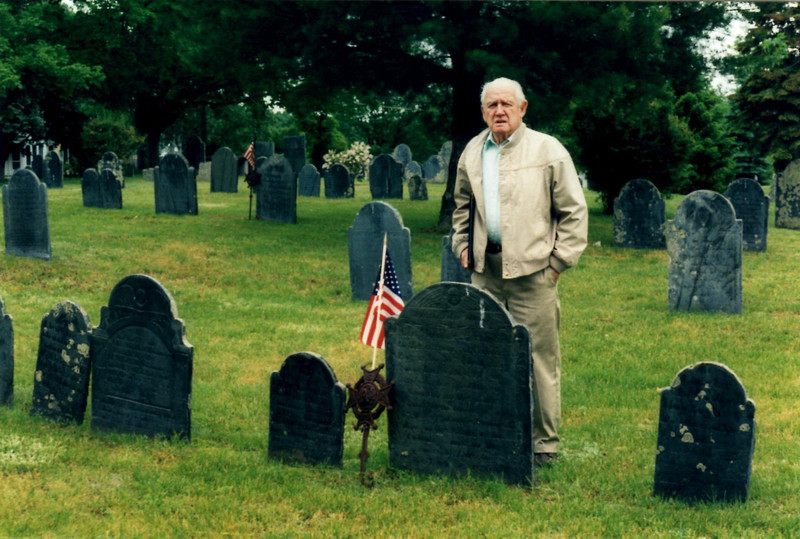 My father standing behind Rogers' gravestone. To locate the grave, enter the cemetery from Main Street using the middle gate (not from the one at the corner of Tadmuck Rd.) the cemetery road will immediately fork. Bear left at this point and park the car. Look to your left for a row of large trees. Walk up the slope behind the middle tree and look three rows back for Rogers' gravestone.