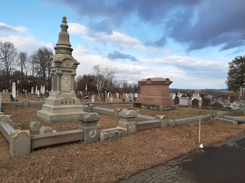"To locate the grave, drive in the center gate and look to your left for these distinctive monuments. The ""bench"" is seen in this photo just to the right of the large red granite monument."