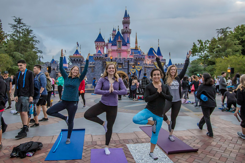 For International Yoga Day, June 21, 2019, more than 1,000 Disneyland Resort cast members registered to practice yoga in front of Sleeping Beauty Castle at sunrise. (Josh Sudock/Disneyland Resort)