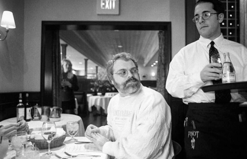 "Ron Clements,Co-Director of ""Hercules�, at the Animator ""thank you� lunch; 1997. The waiter is trying to decide if Ron deserves the water 🤔.Accountant Andrea Paul spies from the doorway, behind the curtain 🤣."