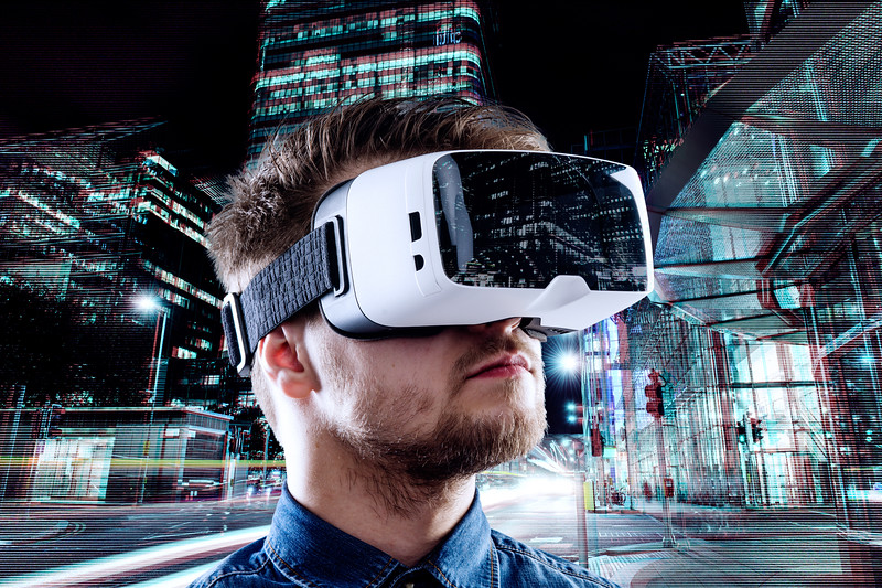 Man wearing virtual reality goggles against night city