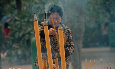 worshipper offering incense at a buddhist temple in Hong Kong 2005