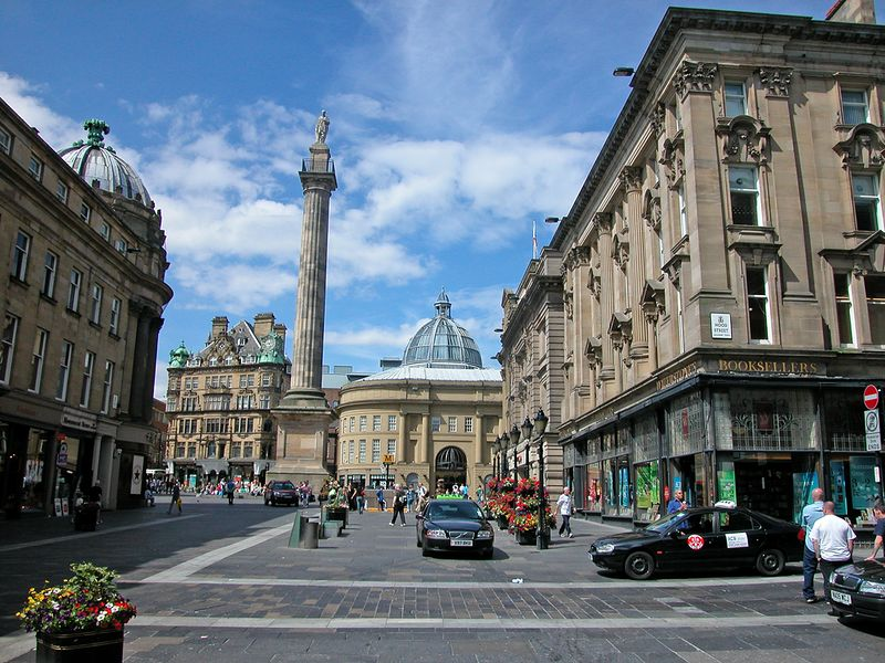 Newcastle center city - Grey Street with its Regency classical facades like those of London, later 19th century buildings, living floral arrangements and Grey's monument (Prime Minister Earl Grey of Howick Hall in Northumberland for whom the tea was named!).