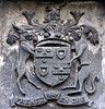 Stone coat-of-arms panel from over the door of the barn that forms an L with Ogle Castle.