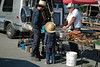 Young Swartzentruber man and his son looking at fishing gear at flea market Kidron.