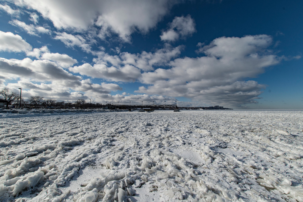 Frozen Lake Erie with lake effect clouds building over the shoreline
