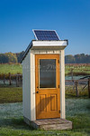 A rural telephone booth with a solar panel in Amish country near Kidron, Ohio, USA.