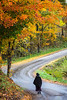 An Amish lady walking on a road with fall foliage color near Strasburg, Ohio, USA.