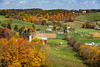 Amish farms in a valley with fall foliage color near Walnut Creek, Ohio, USA.