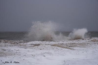 Waves splash frozen shore of Lake Erie.