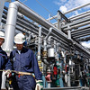 Two industry workers inside oil and gas installation, pipeline main fuel depot