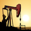 Working oil pump in deserted district at sunset