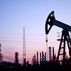 Oil pump on  background of  industrial landscape and sunset sky