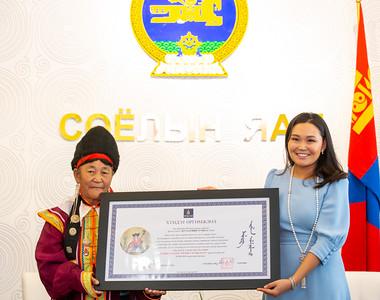 """2021 оны есдүгээр сарын 2. Соёлын сайд Ч.Номин Монгол Улсын соёлын биет бус өвийн 2020 оны шилдэг өвлөн уламжлагч, Увс аймгийн Малчин сумын харьяат, Баяд бийч, ихэлч Ж.Хумбааг хүлээн авч уулзан, хүндэтгэл үзүүллээ.  Соёлын сайдын 2021 оны 02 дугаар сарын 05-ны өдрийн А/18 тоот тушаалаар Монгол Улсын соёлын биет бус өвийн шилдэг 3 дахь өвлөн уламжлагчийг тодруулан, алдаршуулж, """"Хүндэт өргөмжлөл"""", мөнгөн шагнал болох гучин сая төгрөгөөр шагнан урамшуулахаар шийдвэрлэсэн юм. Ковид-19 цар тахлын улмаас тодорхойгүй хугацаагаар хойшлогдоод байсан шагнал гардуулах ёслолын ажиллагааг өнөөдөр Соёлын яам дээр зохион байгуулав.    Жутаагийн Хумбаа нь 1942 онд төрсөн, 79 настай. Баяд бий биелгээ, ихэлийн татлагыг 10 настайгаасаа эхлэн аав, ээжээсээ сурч, эдүгээ 70 шахам жил өвлөн уламжилж, түгээн дэлгэрүүлж байгаа юм. Ж.Хумбаа нь 1959 оноос эхлэн сум орон нутагтаа нэгдлийн малчин, сургуулийн тогооч, эмнэлгийн асрагч, зочид буудлын үйлчлэгч зэрэг ажил хийж улс орондоо 30 гаруй жил хөдөлмөрлөж, гавьяаныхаа амралтад гарсан.  Тэрбээр Улаанбаатар хотноо зохиогдсон """"Алтан тулга"""" ардын урлагийн их наадам /1980, 1981/, Ардын язгуур урлагийн улсын 1, 2-р үзлэг /1983, 1988/, Олон улсын кино наадам /1989/, Ардын хувьсгалын 80 жилийн ойн хүрээнд зохион байгуулагдсан Ардын урлагийн их наадам /2001/, ЮНЕСКО-гийн Монголын морин хуур хөгжмийн уламжлалт урлагийг хамгаалах наадам /2007/, язгуур урлагийн """"Ойрад түмэн"""" наадам /2016/, """"Нүүдэлчин Монгол-2018"""" соёлын биет бус өвийн наадам зэрэг улсын болон олон улсын чанартай наадамд тус тус оролцож, алтан тулга, алт, мөнгө, хүрэл медаль хүртэж, Язгуур урлагийн уламжлалт арга барил, дэг сургууль, намба төрхийг төгс эзэмшсэн """"Өвлөн уламжлагч"""", Монгол Улсын шилдэг """"Өв тээгч"""" медаль, ЮНЕСКО-гийн """"Хүндэт өргөмжлөл""""-өөр тус тус шагнагдаж байжээ. 1990 онд БНХАУ, 2002 онд ОХУ-ын Тува улсад аялан тоглолт хийсэн.    Ж.Хумбаа нь баяд биелгээ, ихэлийн татлагаа хойч үедээ өвлүүлэн үлдээхэд хувь нэмрээ оруулж гэрээр шавь сургалт явуулахын зэрэгцээ Улаангом сумын """