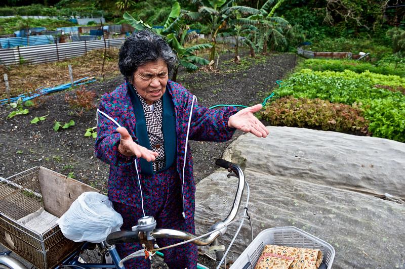Mme Taira (91 ans) en train d'interpréter une chanson célèbrant les bienfaits de la nature devant un potager du village d'Ogimi. Ile d'Okinawa/Japon