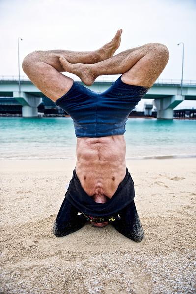 Fumiyasu Yamakawa (88 ans) réalisant un exercice de yoga lors de son entraînement physique quotidien sur la plage de Naminoue à Naha. Ile d'Okinawa/Japon