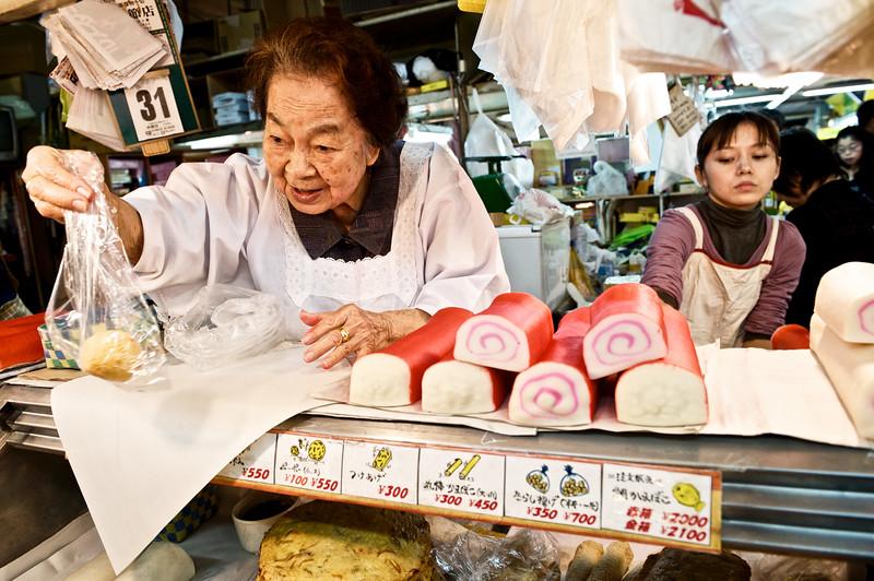 Une vendeuse de kamaboko (pâtes de poissons) de 92 ans derrière son stand du marché Makishi à Naha. Ile d'Okinawa/Japon