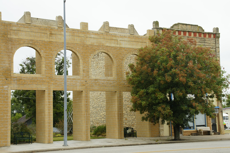 Former limestone building front, now used with a city park behind