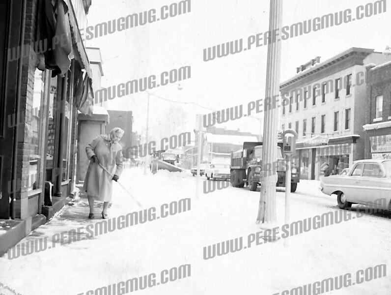 Lea Ann Szurek Rosenthal wrote about this photo on Oct 21st;<br /> <br /> That is a fantastic picture of my grandmother, Mary Slezak, shoveling the snow from in front of Slezak's Mens Wear. She and her husband, William Slezak, operated the clothing, shoe, and fishing supply store at 140 East Main St. in downtown Amsterdam on the west side of St. Mary's Church. When my grandfather died in 1957, my grandmother continuee to operate the store until 1969 at which time Urban Renewal bought her buildings.