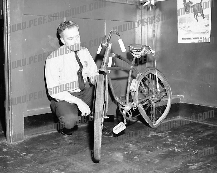 Then Ptlm. Marvin Swart, later Deputy Chief, examining bicycle of boy killed after being hit by truck on Northampton Road, mid 1960's.