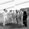 5th from left is Bill Miskinis, AHS Class of 62, I think. He was the team shot putter and discus thrower. I think he was the quarterback on the football team too. I believe he set the school record in the shot put at that time but I don't remember the distance. Coach Ed Cionek is 5th from right. The picture is taken at the track/football field behind the high school. To the left of the group is either the pole vault pit or high jump pit. We used sawdust for the pits then and a pitchfork to fluff it up.